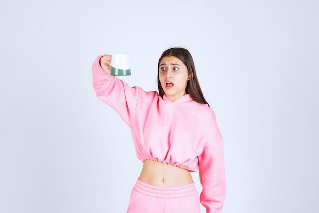 Meisje in roze pyjama neemt een lege koffiemok en wordt teleurgesteld.