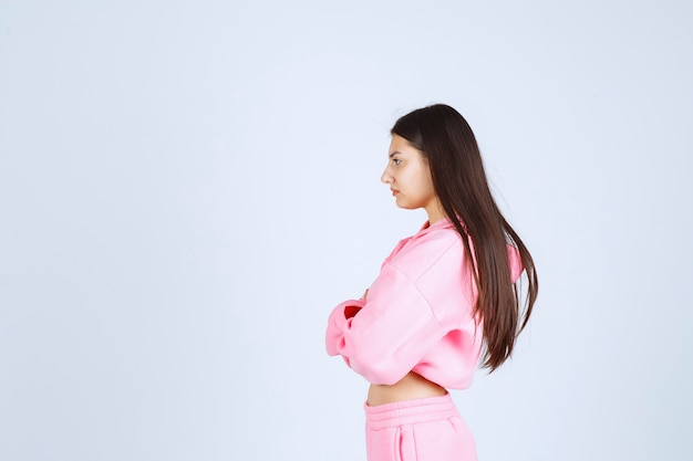 Meisje in roze pyjama's die de armen kruisen en ziet er agressief uit.