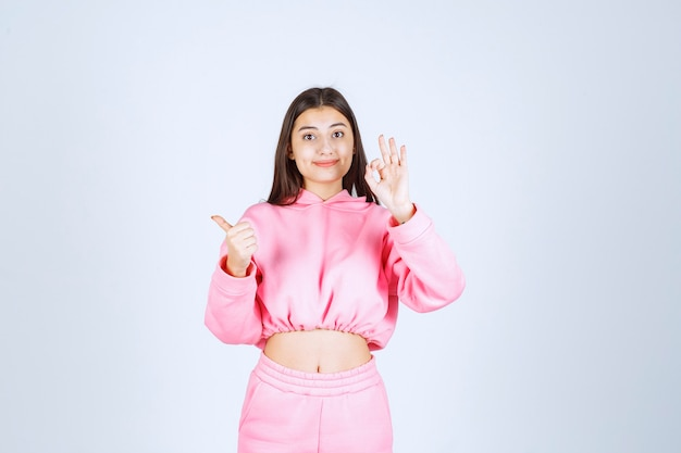 Meisje in roze pyjama's die duim tonen