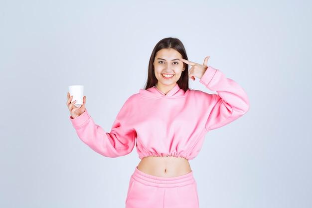Meisje in roze pyjama's die een koffiekop houden en denken