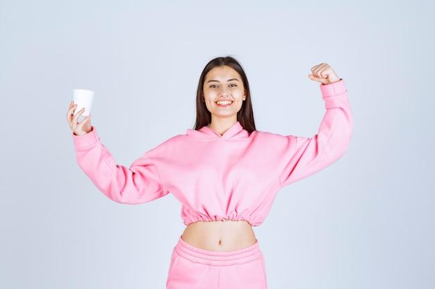 Meisje in roze pyjama's die een koffiekop houden en haar vuist tonen