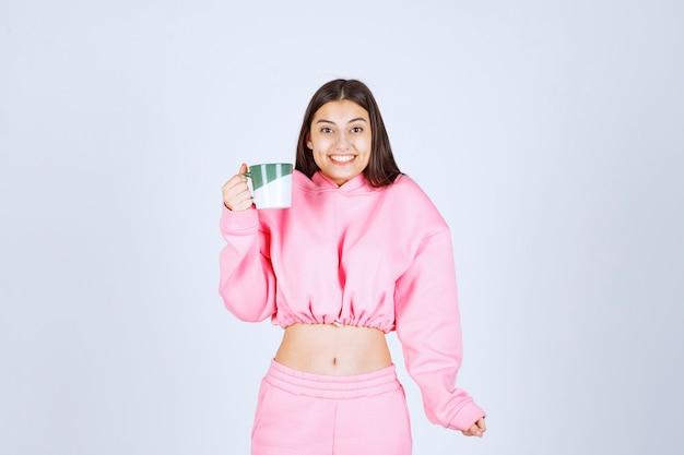 Meisje in roze pyjama's die een koffiemok houden en zich gelukkig voelen.