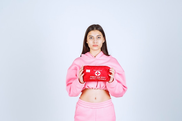 Meisje in roze pyjama's die een rode ehbo-doos vasthouden en deze promoten.