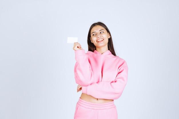 Meisje in roze pyjama's die een visitekaartje houden en zich voorstellen aan haar zakenpartners.