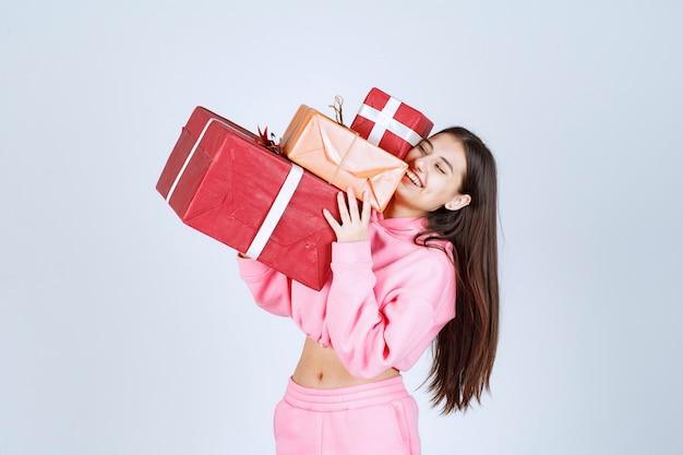 Meisje in roze pyjama's die meerdere rode geschenkdozen houden en zich gelukkig voelen.