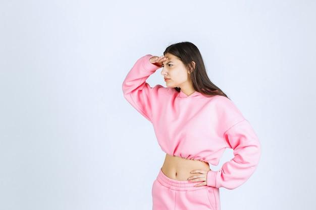Meisje in roze pyjama's die vooruit kijken