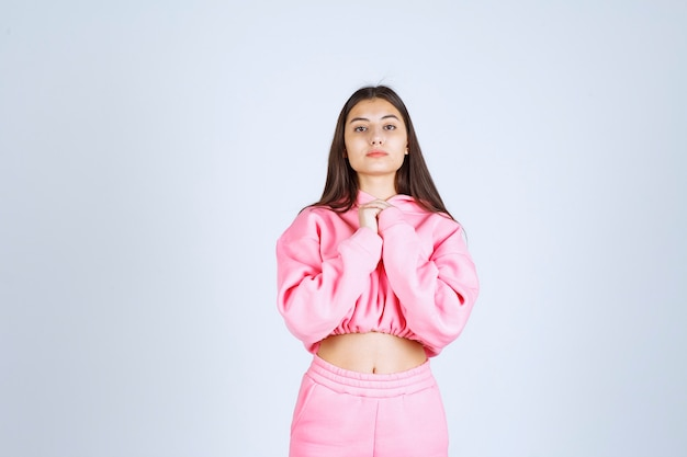 Meisje in roze pyjama's die vrolijke en verleidelijke poses geven