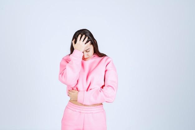 Meisje in roze pyjama's houdt haar hoofd vast als ze uitgeput is of hoofdpijn heeft.