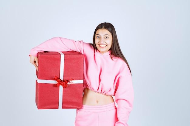Meisje in roze pyjama's knuffelen een grote rode geschenkdoos en glimlachen.
