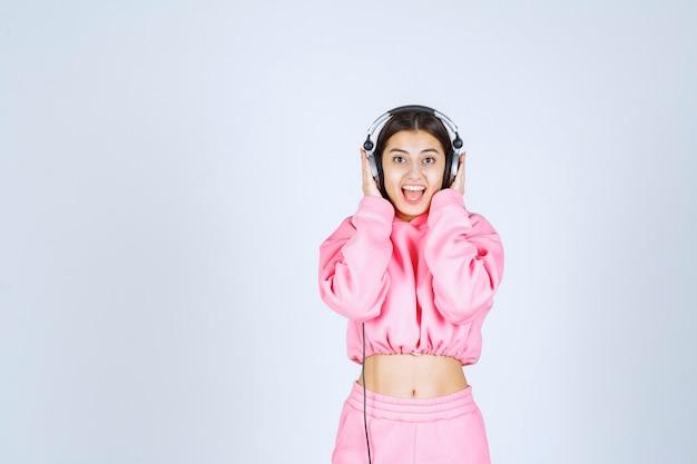 Meisje in roze pyjama's luisteren naar de koptelefoon en plezier maken.