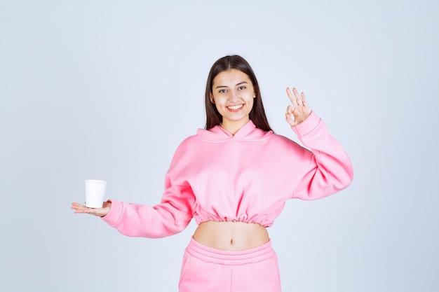 Meisje in roze pyjama's met een koffiekopje en genietend van de smaak