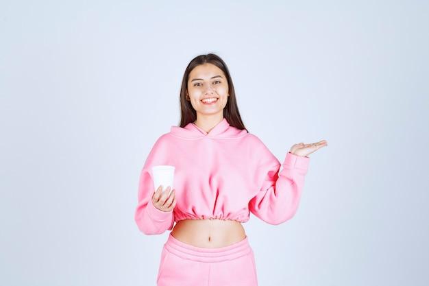 Meisje in roze pyjama's met een koffiekopje en wijzend op iets