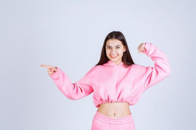 Meisje in roze pyjama's toont haar vuist en voelt zich krachtig.