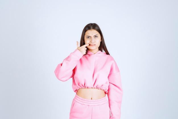 Meisje in roze pyjama's wijzend op haar mond