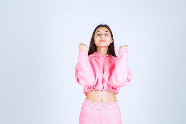 Meisje in roze pyjama ziet er sportief uit en toont haar vuisten