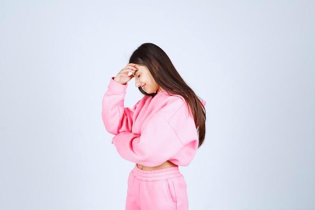 Meisje in roze pyjama ziet er verward en attent uit