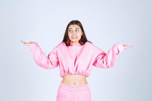Meisje in roze pyjama ziet er verward en onervaren uit