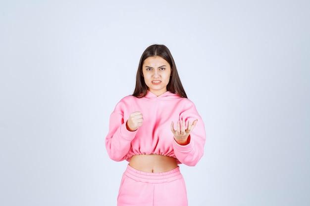Meisje in roze pyjama ziet eruit als een vechter en agressief