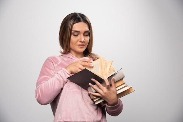 Meisje in roze swaetshirt dat een voorraad boeken vasthoudt, een bovenaan opent en het leest.