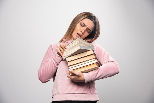 Meisje in roze sweater houdt een voorraad boeken vast, opent er een aan de bovenkant en leest het.