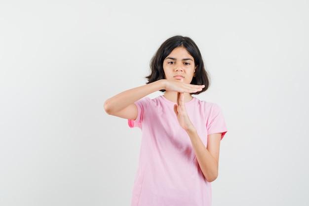 Meisje in roze t-shirt dat het gebaar van de tijdpauze toont en ernstig, vooraanzicht kijkt.