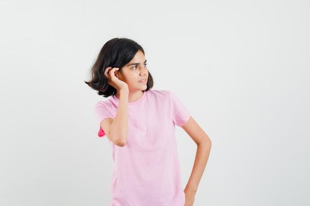 Meisje in roze t-shirt die hand achter oor houdt en nieuwsgierig, vooraanzicht kijkt.