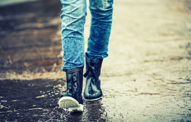 Meisje in rubberen laarzen buiten in regenachtige dag.