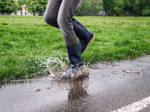 Meisje in rubberen laarzen springen in een plas.