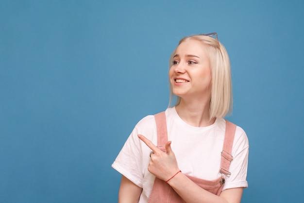 Meisje in schattige kleren staande tegen de van een blauwe muur, haar vinger opzij en glimlachend