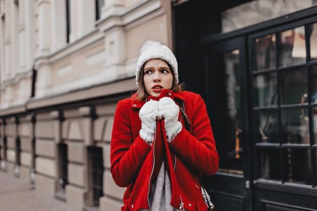 Meisje in sneeuwwitte gebreide muts en wanten schudt van de kou en wikkelt zich in een rode jas.