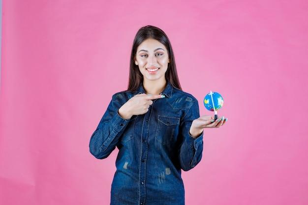 Meisje in spijkerjasje dat een wereldbol vasthoudt en erop wijst