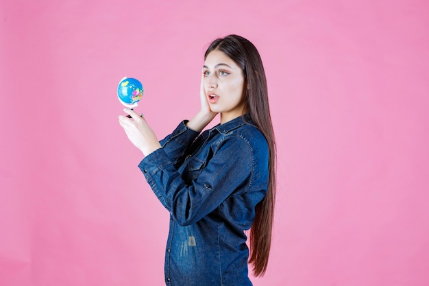 Meisje in spijkerjasje met een wereldbol en kijkt verbaasd