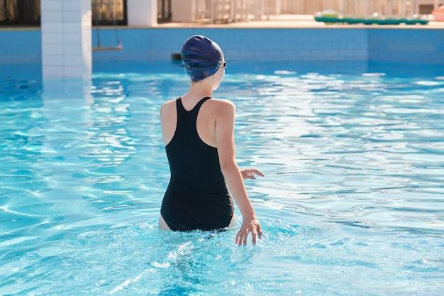 Meisje in sport zwembroek en badmuts invoeren van het buitenzwembad.