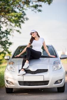 Meisje in sportkleding en een baseballcap staat in de buurt van een auto op de weg