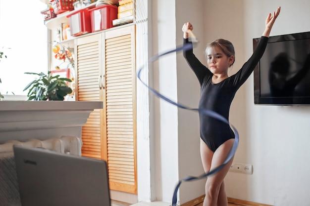 Meisje in sportkleding kijken naar sportwedstrijd online en oefeningen in ritmische gymnastiek herhalen