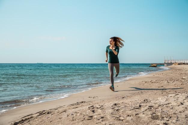 Meisje in sportkleding loopt langs de zee