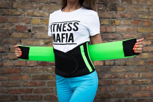 Meisje in sportkleding met een elastische tailleband in de straat.