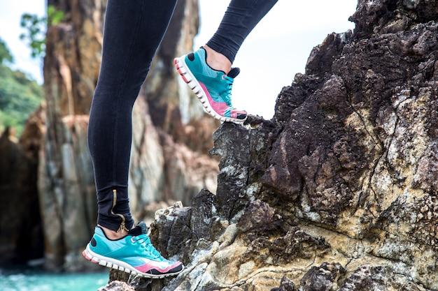Meisje in sportkleding op de rotsen