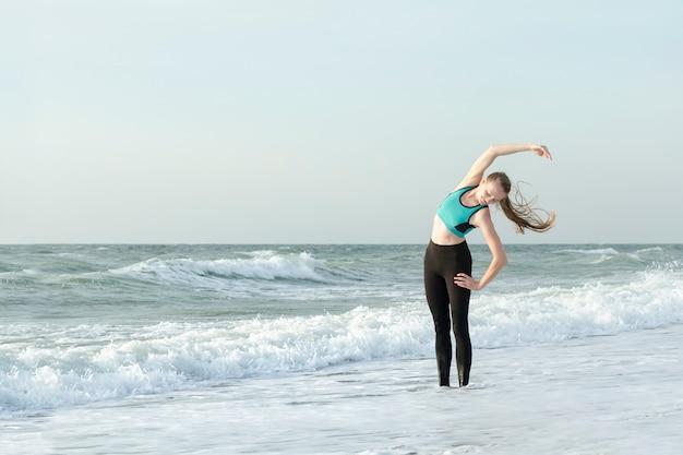 Meisje in sportkleding op het strand dat oefeningen doet. ochtendzon