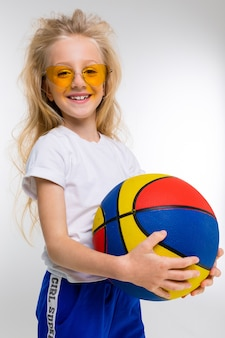 Meisje in sportkostuum met geïsoleerd basketbal