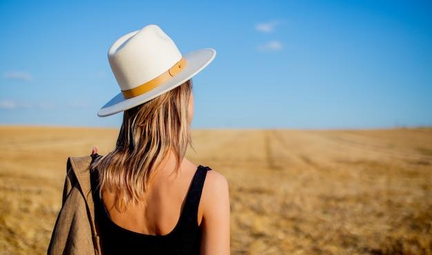 Meisje in stijlhoed bij het gebied van de plattelandstarwe