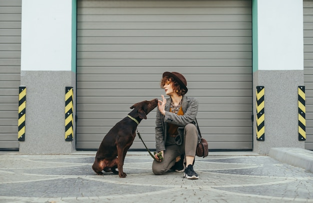 Meisje in stijlvolle kleding zit met een hond op straat en voedt voer uit de handen