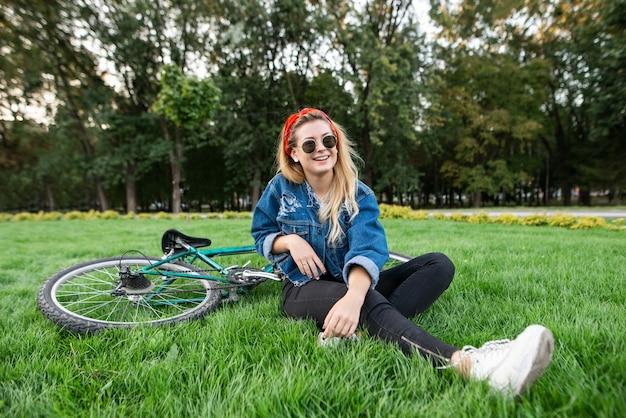 Meisje in stijlvolle kleding, zittend op het groene gazon in een park met een fiets en ontspannen.