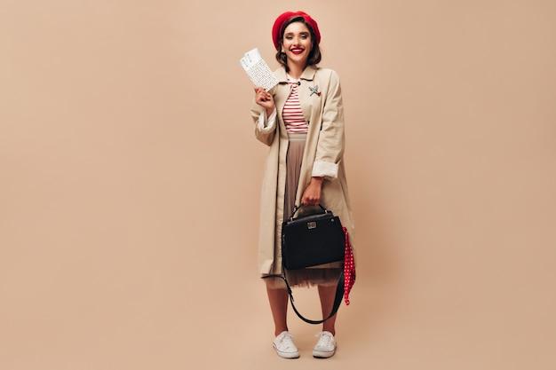 Meisje in stijlvolle outfit vormt met handtas en kaartjes. mooie jonge vrouw in lange beige rok en jas glimlacht op geïsoleerde achtergrond.