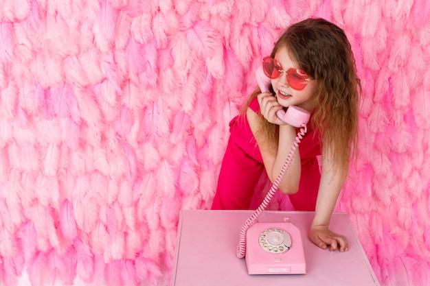 Meisje in stijlvolle roze bril op roze praat over een roze telefoon