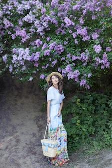 Meisje in strohoed in tuin op zomerdag mooie vrouw in lange jurk staat in lila tuin