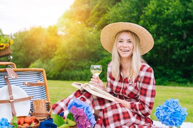 Meisje in strohoed met een wijnglas en een boek zittend in een picknick buiten