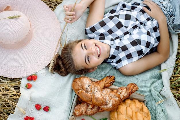 Meisje in strooien hoed op picknick. bovenaanzicht. esthetische picknick buitenshuis met brood en fruit, bessen en croissants.