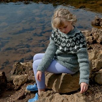 Meisje in sweaterzitting op rotsen door lakeshore