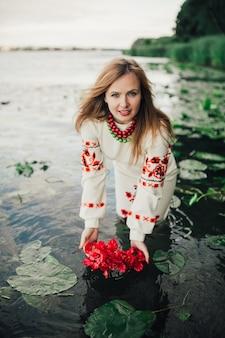 Meisje in traditionele oekraïense kleren brengen bloem krans in het water